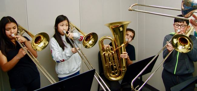 Girls and boys playing trombones and tuba